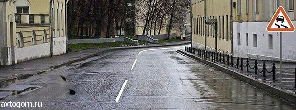 На каком расстоянии до скользкого участка дороги устанавливается данный знак в населенном пункте